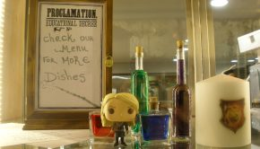 Φωτογραφία: Βιτρίνα με μπουκαλάκια με φίλτρα, μινιατούρα της Λούνα, κερί Γκρίφιντορ και την επιγραφή Check our menu for more dishes σε στυλ εντολής από την Άμπριτζ