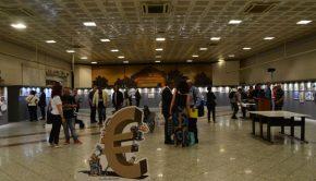 Φωτογραφία της αίθουσας με επισκέπτες στο χώρο. Υπάρχει τρισδιάστατο σκίτσο με ανθρώπους δεμένους (σκλάβους) σε ένα ευρώ.